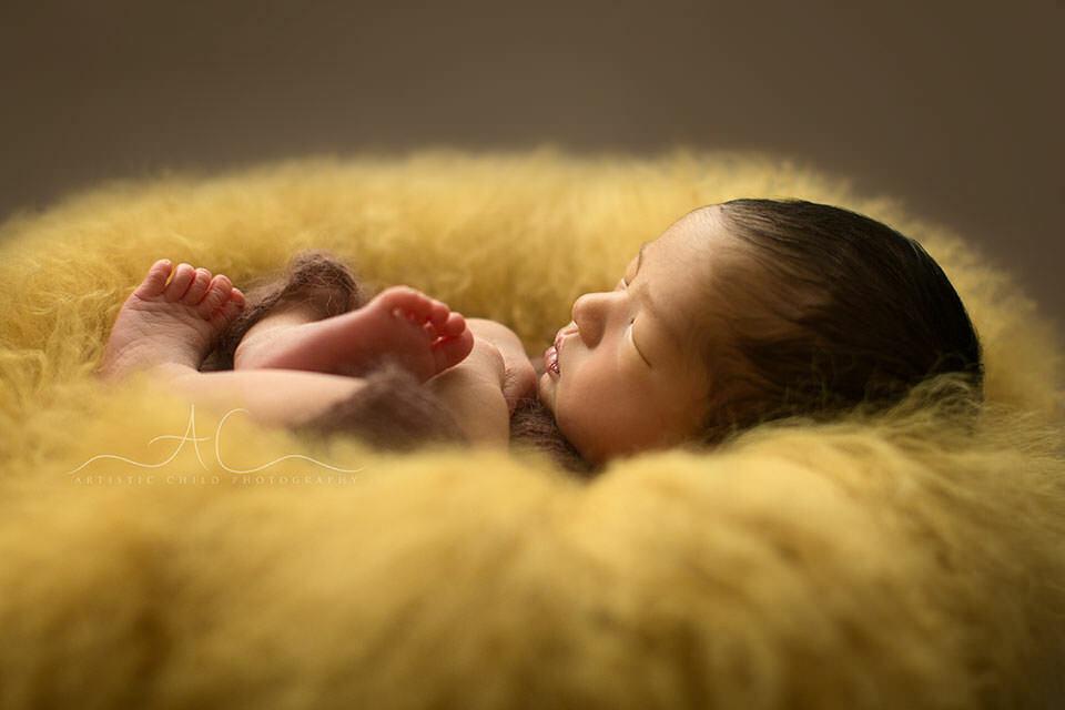 profile portrait of a newborn baby boy sleeping on a yellow curly sheepskin | London