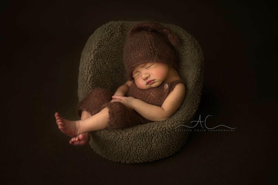 Best London Newborn Portraits | newborn baby boy wearing a sleepy hat and sleeping in a newborn posing pod