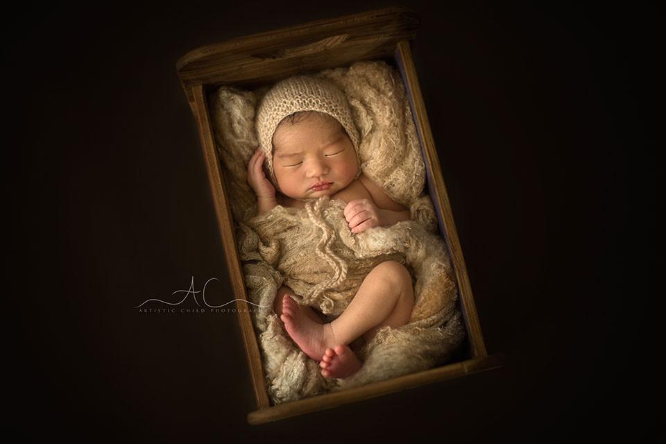 Best London Newborn Portraits | newborn baby boy sleeping in a tiny wooden bed prop