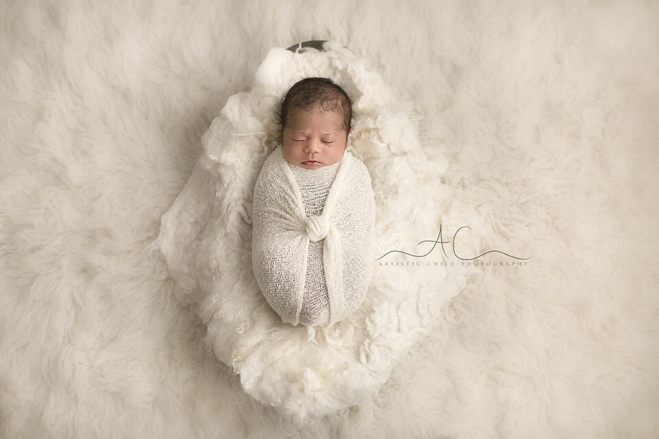 Bromley Newborn Baby Images | swaddled newborn baby boy sleeping in a trench wooden bowl