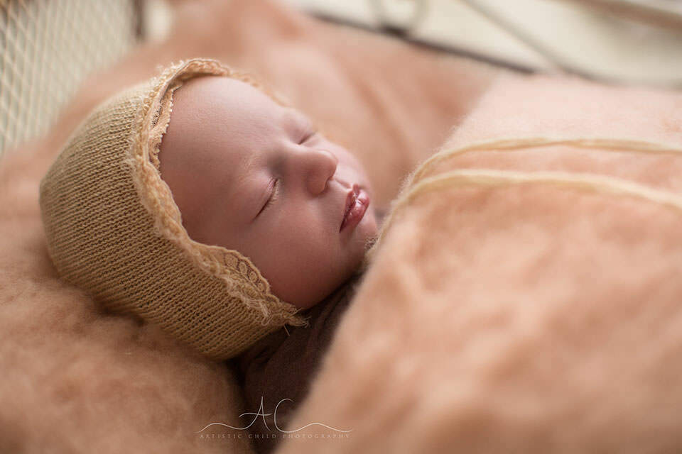 Bromley Newborn Images | backlit portrait of a mewborn baby girl sleeping peacefully in a little metal bed