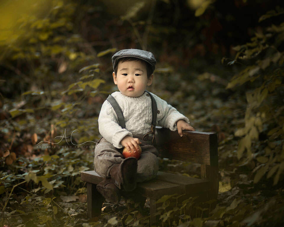 Professional London Toddler Photographer | 1 year old boy in a flat cap sitting on a small wooden bench in London park