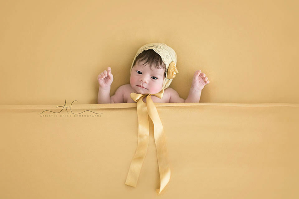 Professional South East London Newborn Photographer | newborn baby girl wearing a beautiful yellow lace bonnet