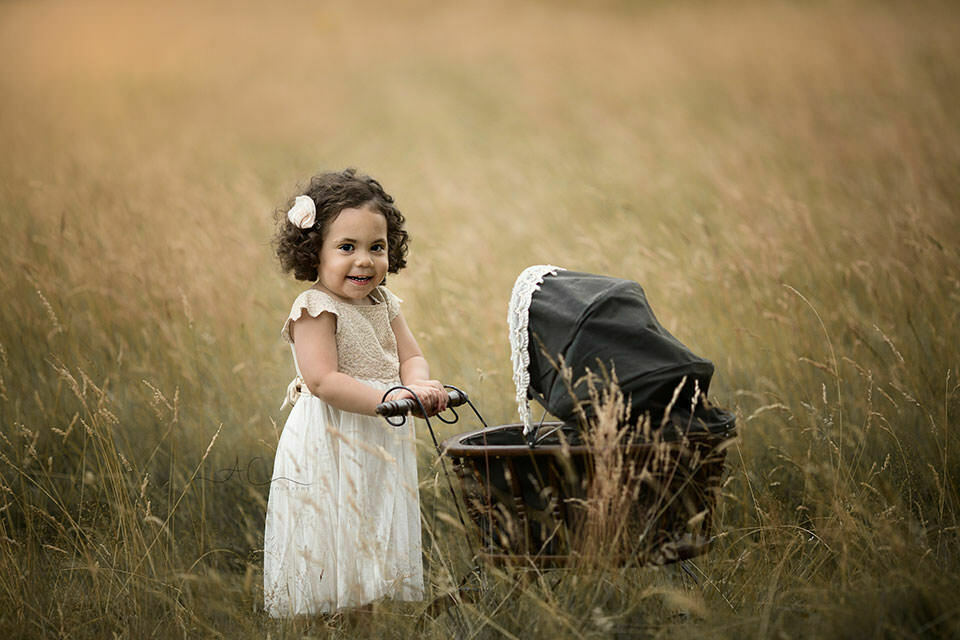 2 year old girl playing with a vintage pram in the park   London