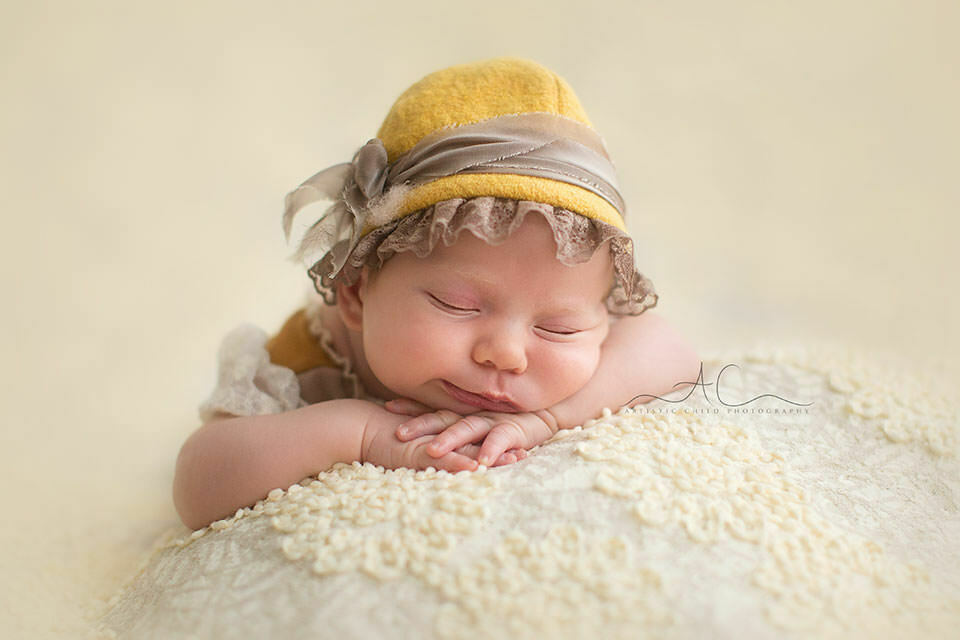 Best South East London Newborn Photos | portrait of a newborn baby girl wearing a beautiful mustard colour hat while sleeping in hands under chin position