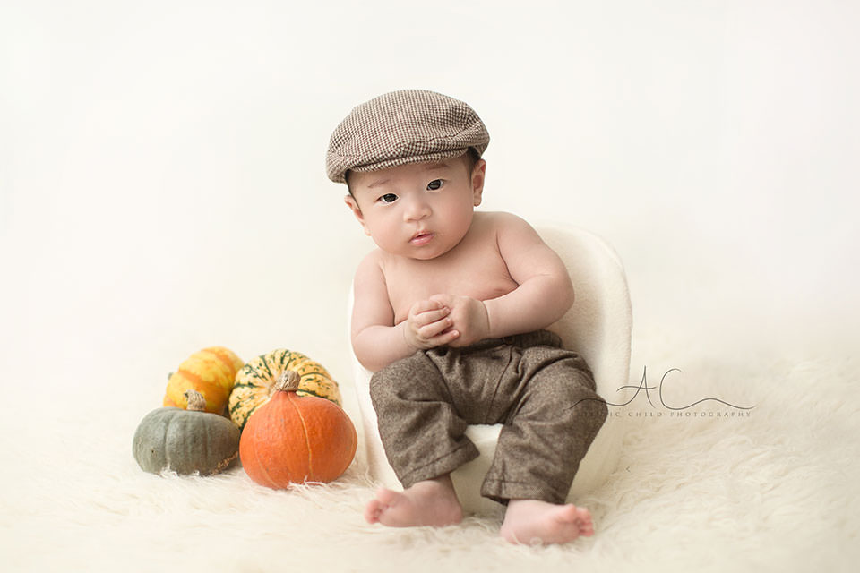 London 100 day Asian Baby Photographer | 100 days old baby boy in a flat cap sitting in the posing pod
