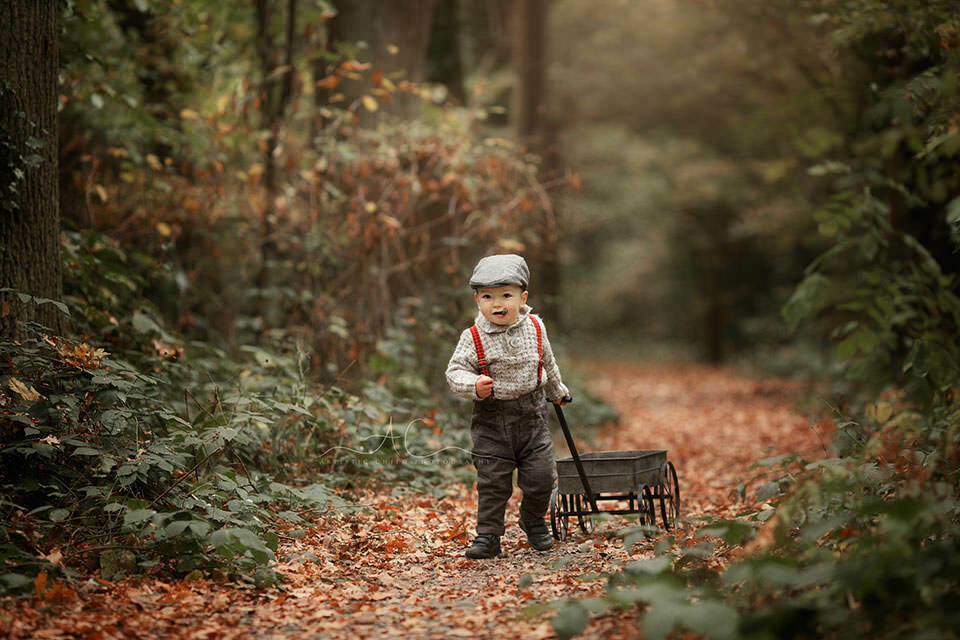 Professional London Toddler Photo Session | 18 months old baby boy pulling a metal trolley while playing in the park during autumn season