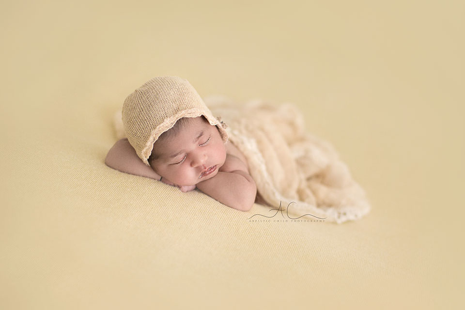 Professional South East London Newborn Images | newborn baby girl sleeping tightly covered by the beautiful scarf