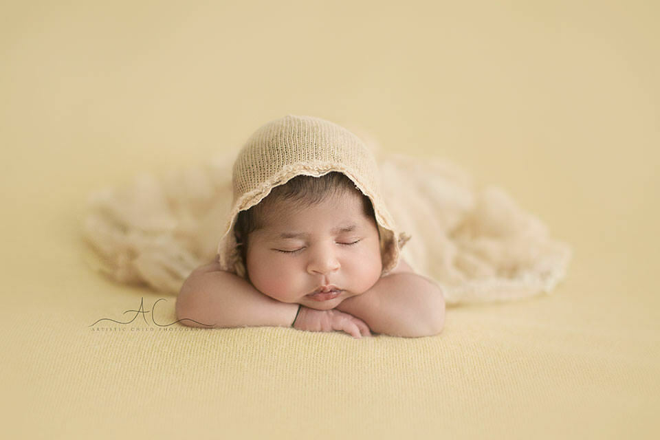Professional South East London Newborn Images | newborn baby girl wearing a beautiful bonnet posed in hands under chin pose