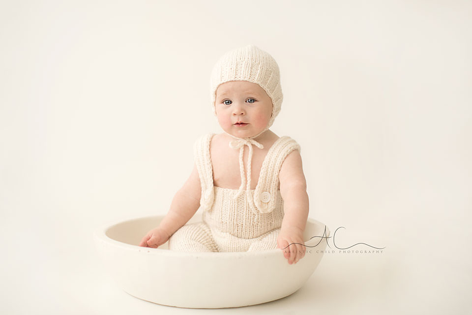portrait of a 6 months old baby boy sitting in a white wooden bowl | London