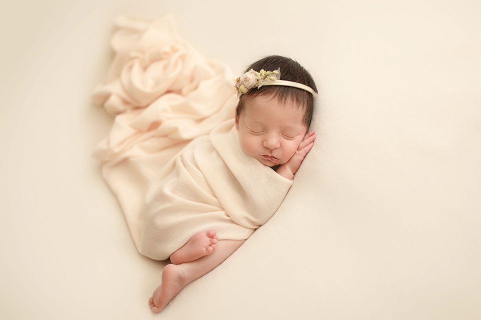 Professional Bromley Newborn Photos | newborn baby girl sleeping under cream wrap and wearing a beautiful matching hairband