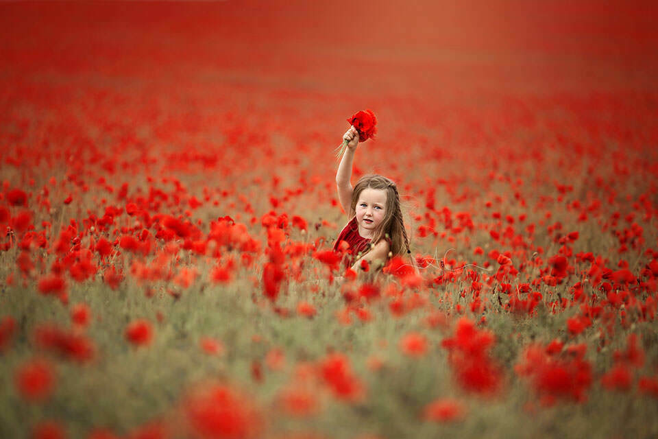 5 year old girl running through a poppy field with a bunch of poppies in her hand | London
