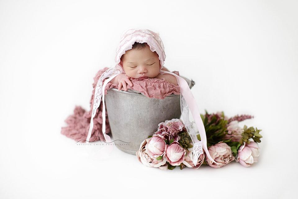 newborn baby girl sleeping in an old antique metal bucket | London