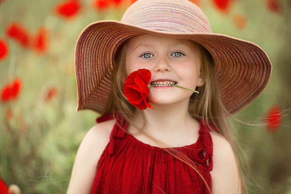 Best London Kids Pictures | 5 year old girl smiling with a poppy flower in her mouth