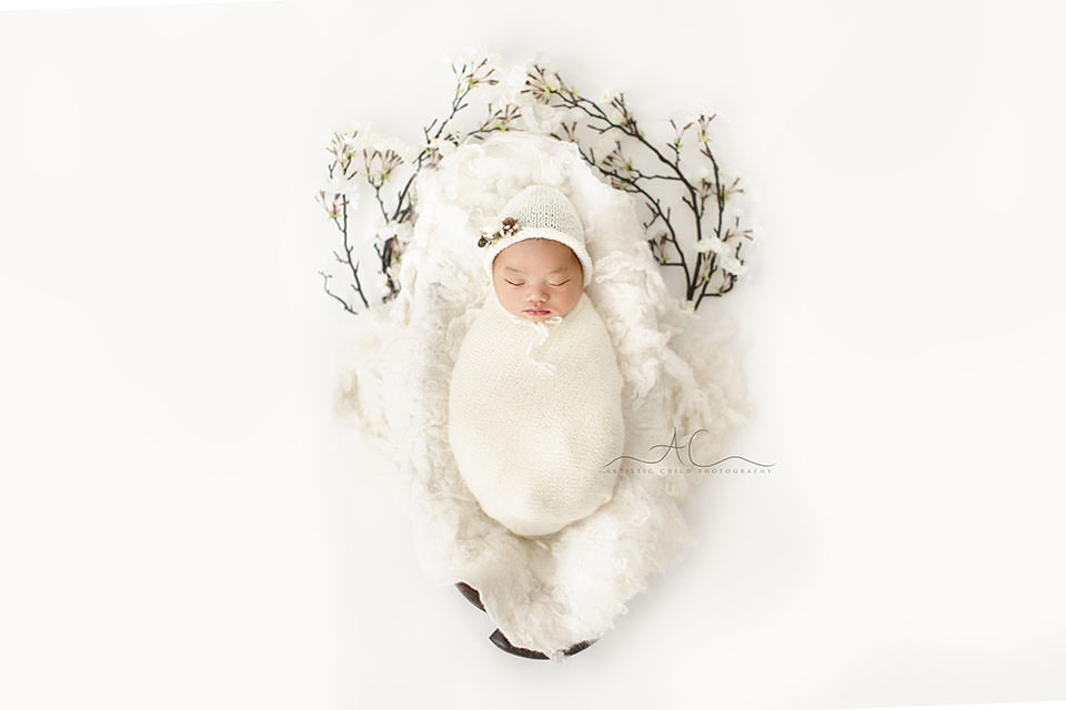 Bromley Newborn Baby Pictures | newborn baby girl sleeping in a wooden trench bowl swaddled in white knitted wrap