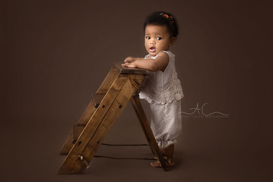 London Baby Girl Portraits | 6 months old baby girl standing while holding onto small wooden ladder steps