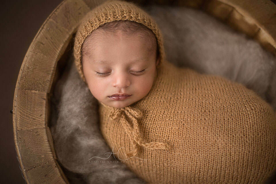 portrait of a newborn baby boy wearing a hand knitted hat   London