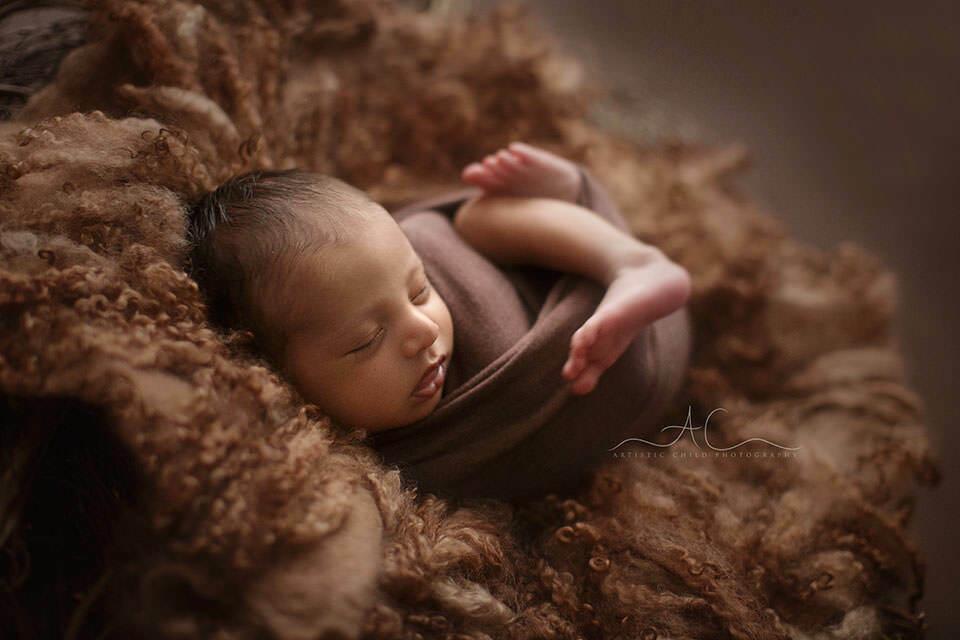 backlit portrait of a newborn baby boy sleeping swaddled   London