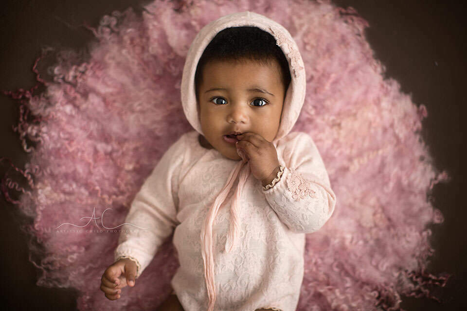 portrait of a 6 months old baby girl wearing a cute pink outfit and hat | London