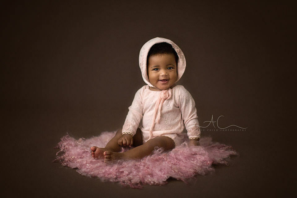 6 months old baby girl wearing a cute pink outfit and hat smiles while sitting on the floor | London
