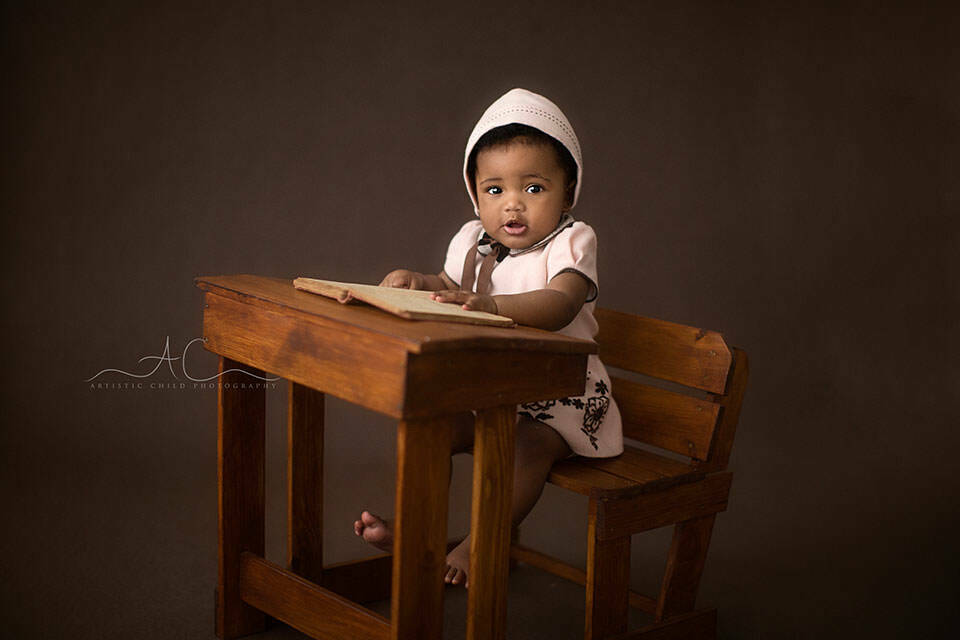 6 months old baby girl sitting at a small wooden desk | London