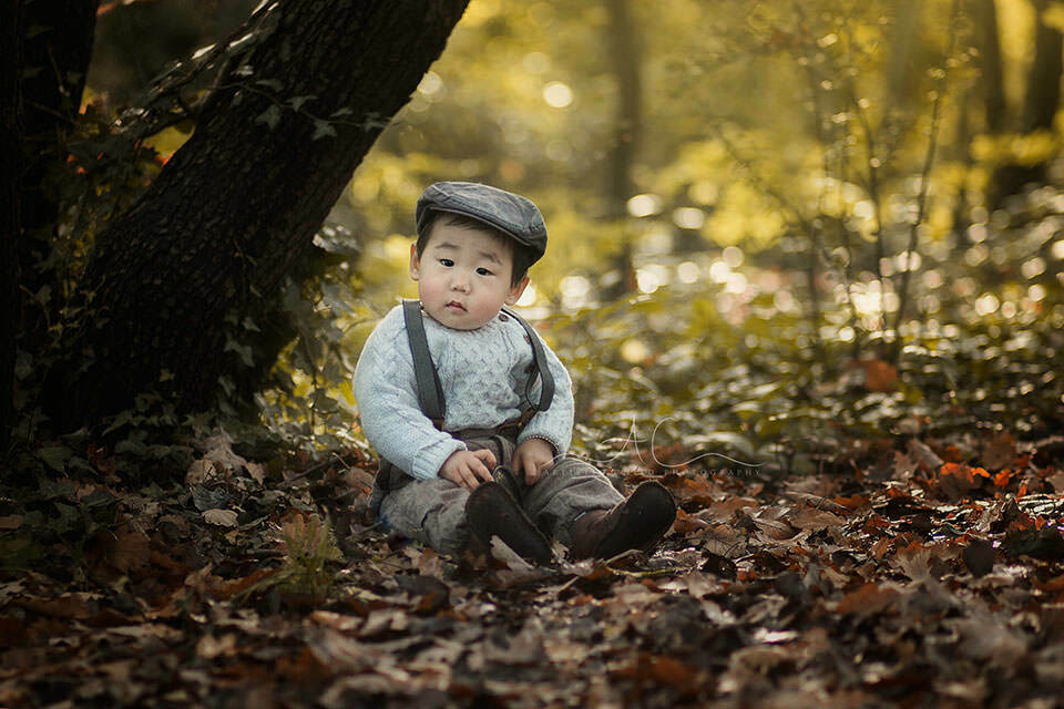 autumn portrait of a 1 year old boy wearing a flat cap in London park