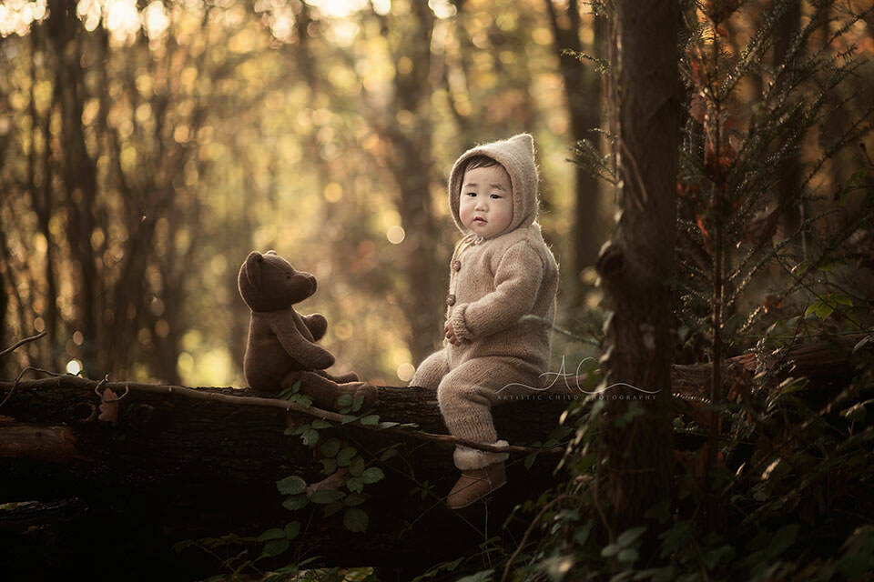 1 year old boy sitting on a wooden log together with his teddy bear | London