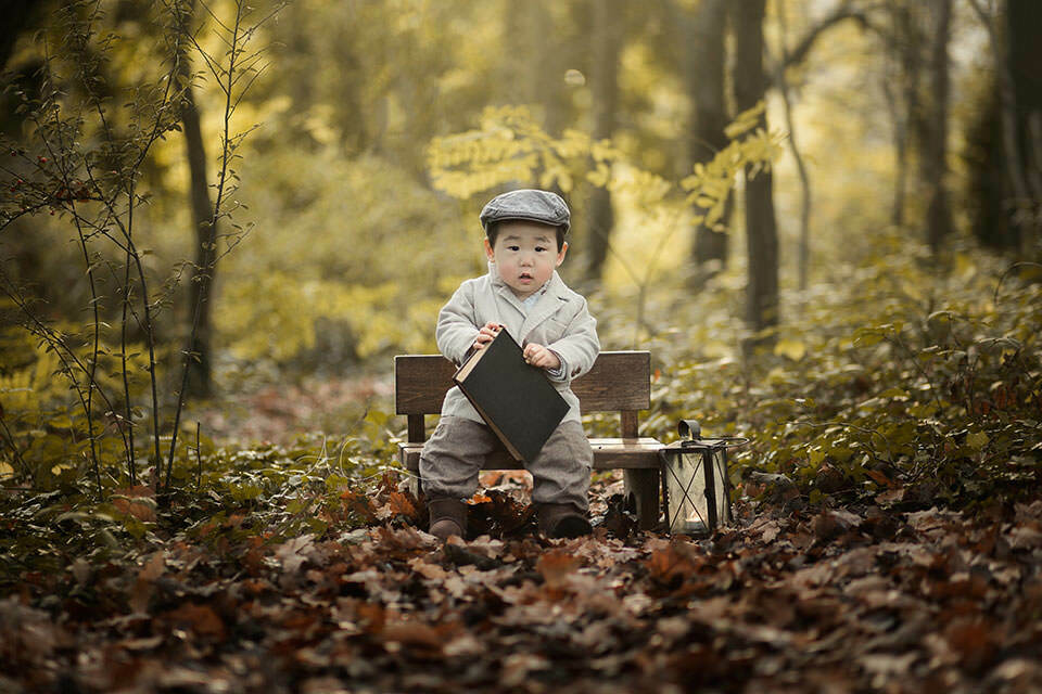 Professional London Toddler Portraits | 1 year old boy sitting on a small wooden bench and holding a book while playing in the park