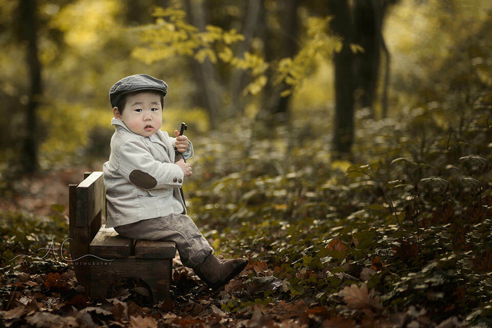 Professional London Toddler Portraits | outdoor portrait of 1 year old boy sitting on a small wooden bench and holding a bunch of big iron keys