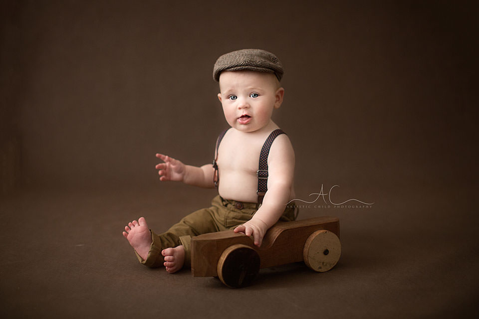 6 months old baby boy in flat cap playing with a wooden car toy | London