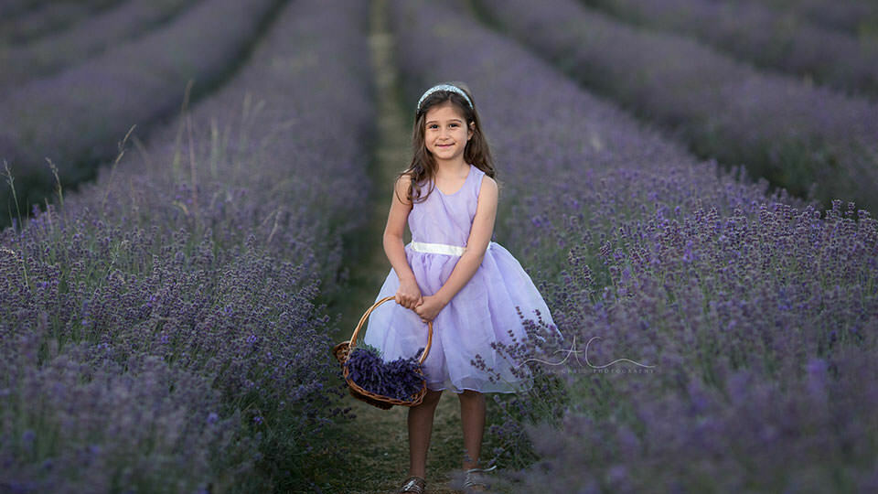 5 year old girl carrying a flower basket full of lavender flowers | London