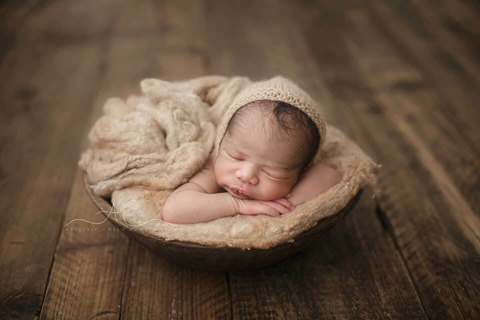 Beautiful London Newborn Pictures | newborn baby boy sleeping in a wooden bowl