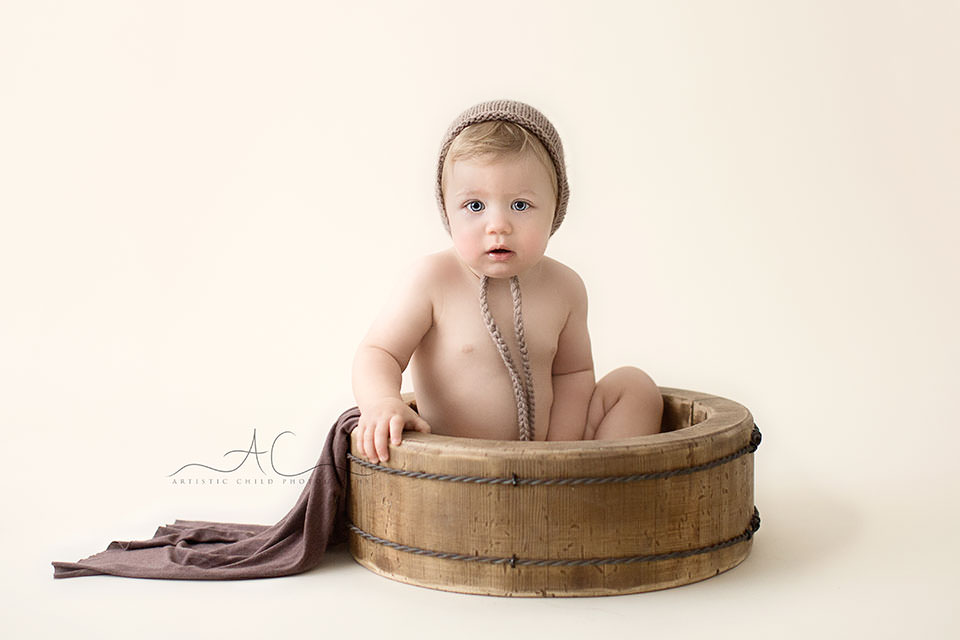Bromley Toddler Pictures | 1 year old boy sitting in a wooden bowl