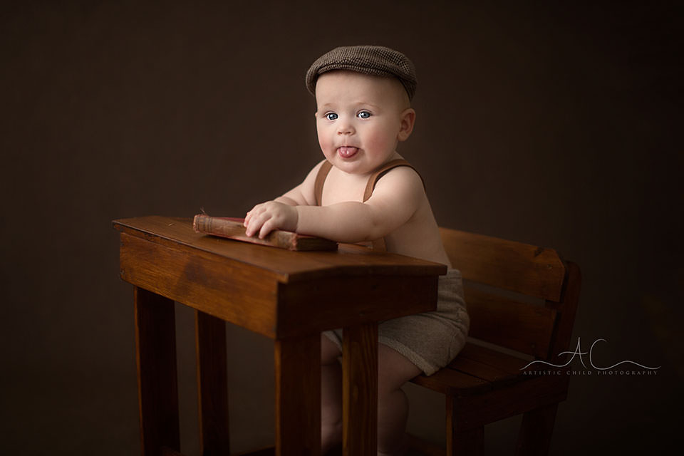 Professional South East London Baby Photos |6 months old baby boy showing his tongue while sitting at a wooden desk