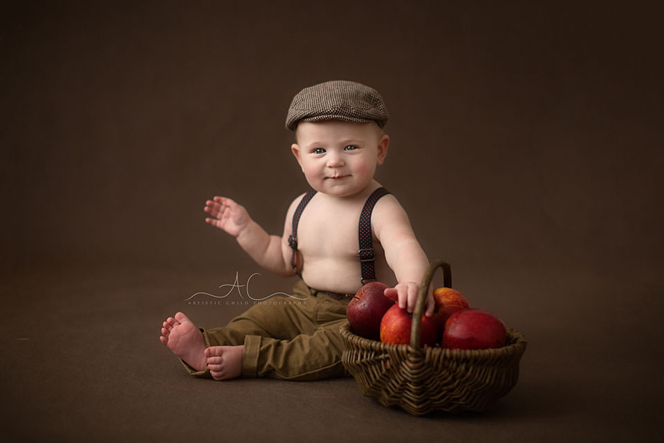 Professional South East London Baby Photos |6 months old baby boy playing with wicker basket full of red apples