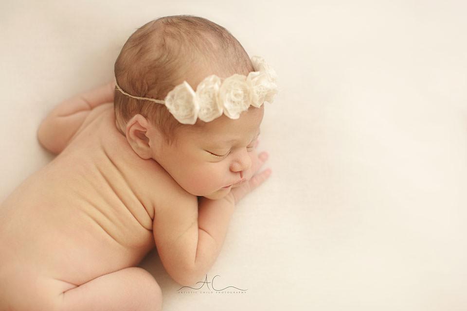 portrait of a newborn baby girl wearing a cute flower hairband | London
