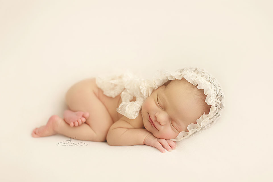 South East London Newborn Baby Girl Photos | portrait of a newborn baby girl wearing a cute lace bonnet while sleeping on her tummy