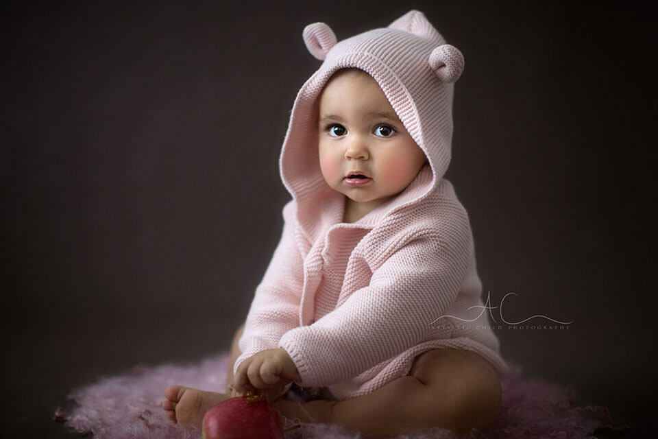 portrait of 1 year old toddler girl wearing a pink bear cardigan | London