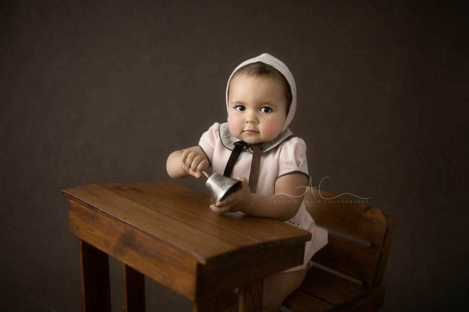 South East London Toddler Portraits | 1 year old girl playing with the bell while sitting a the old school desk
