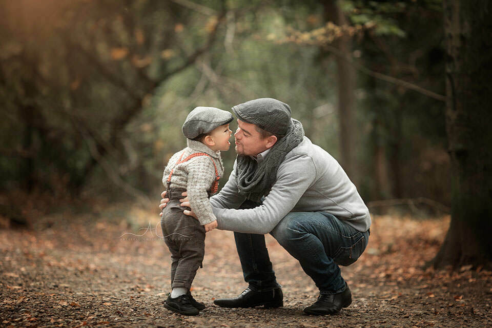 portrait of a father kissing his 18 months old son in woodland looking park | London