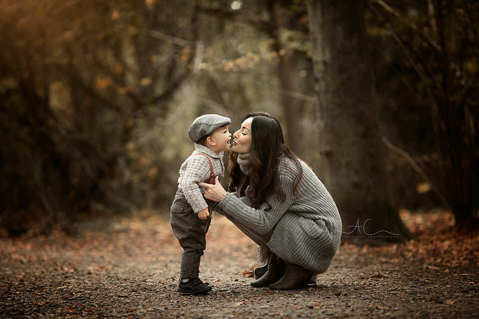 mum kissing her 18 months old son in woodland looking park | London