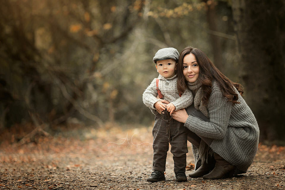portrait of a mum and her 18 months old son taken in a woodland looking park in South East London