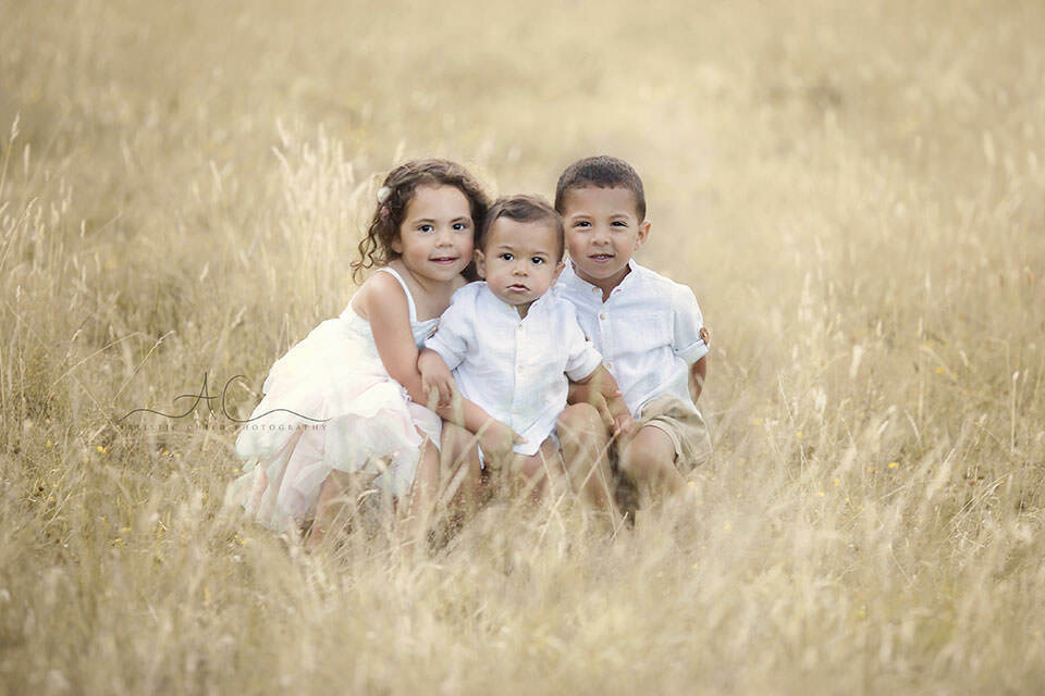 portrait of 2 brothers and a sister taken outdoor during the playtime | London