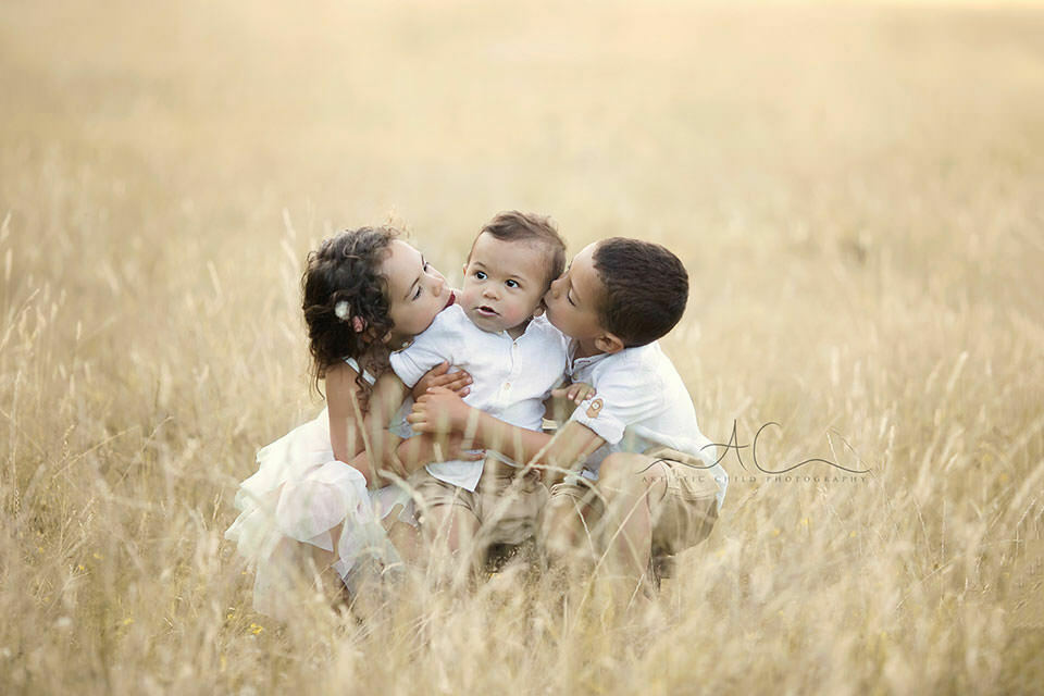 outdoor portrait of older brother and sister kissing a 1 year old baby boy | London