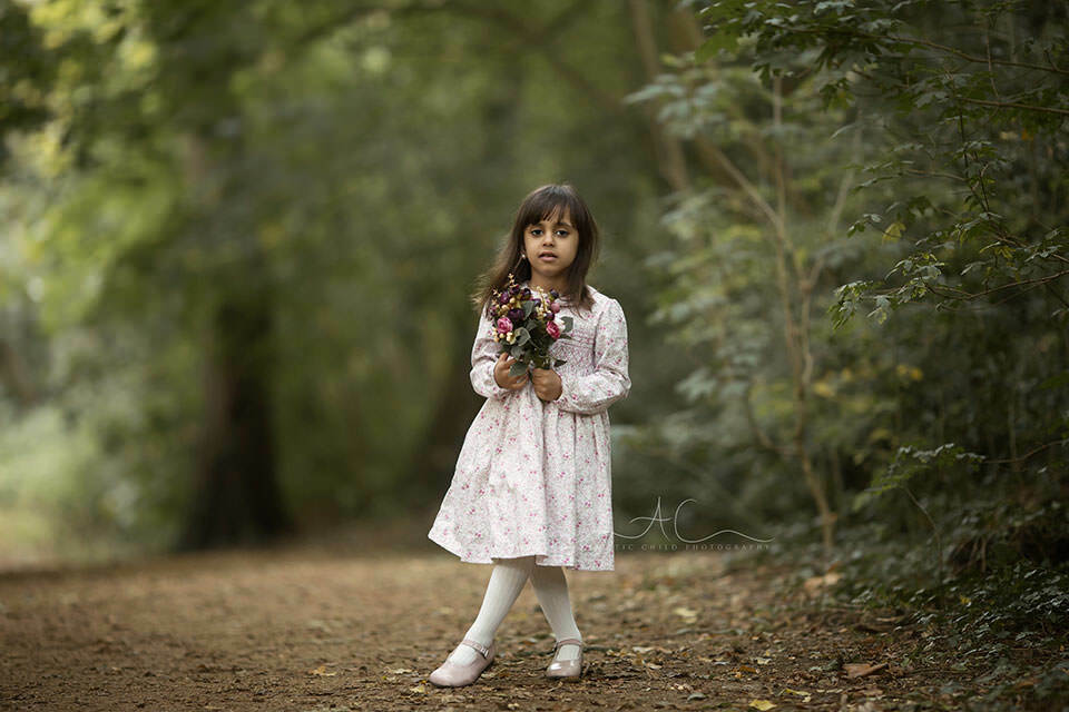 5 year old girl with flowers standing in the middle of the park | London