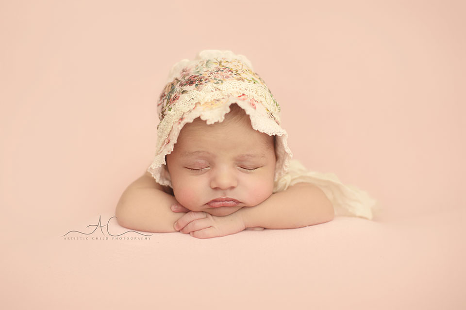 portrait of a newborn baby girl posed in hands under chin position | London
