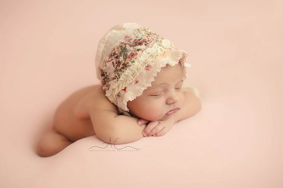 side portrait of a newborn baby girl posed in hands under chin pose | London
