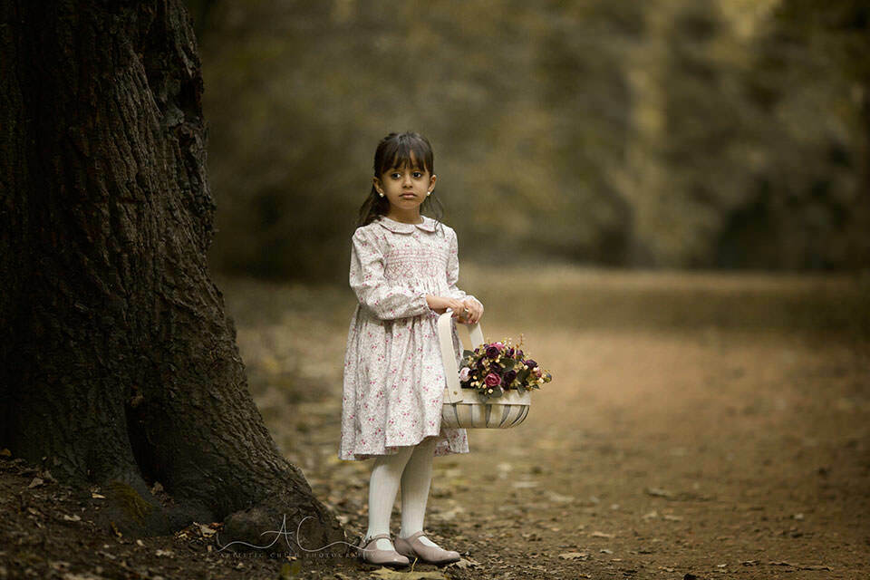 Bromley Children Portraits | 5 year old girl holding a basket full of flowers while playing in the park