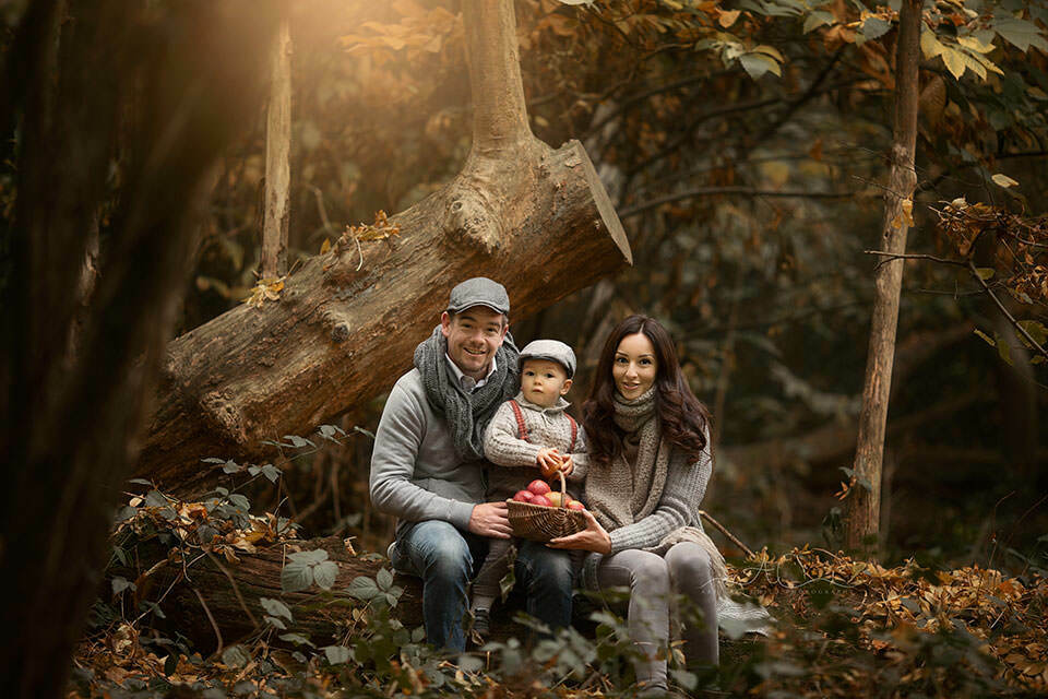 London Family Photography Services | family of 3 sitting on a wooden log in woodland looking park in South East London