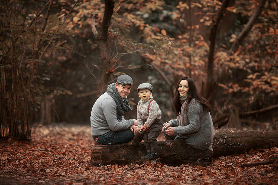 London Family Photography Services | portrait of parents and their 18 months old son sitting on a wooden log taken during autumn season